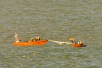 1205: a lifeboat crew is in the water lowering the sail
